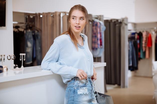 옷가게에 서있는 쇼핑 가방과 함께 편안한 행복 한 젊은 여자