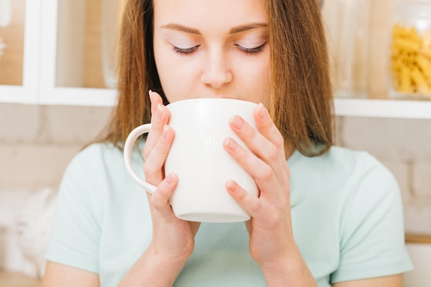 Relaxed home leisure. morning tradition. woman enjoying a cup of hot beverage in white cup