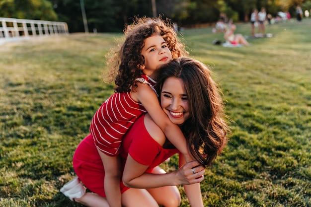 Ragazzo rilassato con i capelli ricci che abbraccia la madre sulla natura splendida donna in abito rosso scherzare nel parco con la figlia.