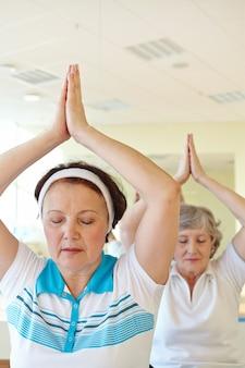 Ослабленный дамы делают упражнения йоги