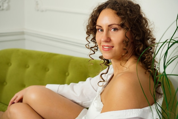 Relaxed lifestyle. happy young woman with curly hair in white shirt spending time at home. green sofa and white walls in room