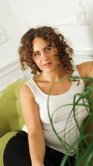 Relaxed lifestyle. happy young woman with curly hair in white t-shirt spending time at home. green sofa and white walls in room - vertical photo