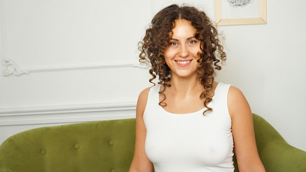 Relaxed lifestyle. happy young woman with curly hair in white t-shirt spending time at home. green sofa and white walls in room
