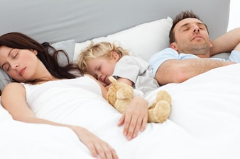 Relaxed little boy sleeping with his parents in their bed