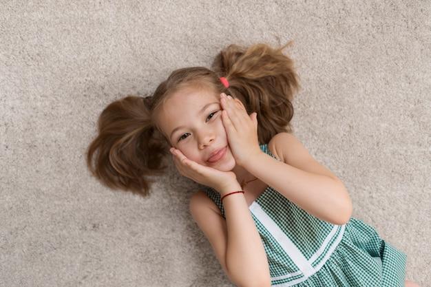 Расслабленная маленькая девочка лежит на полу в помещении и улыбается