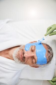 Расслабленный пожилой мужчина с синей пеной покрывает лицо в спа-салоне