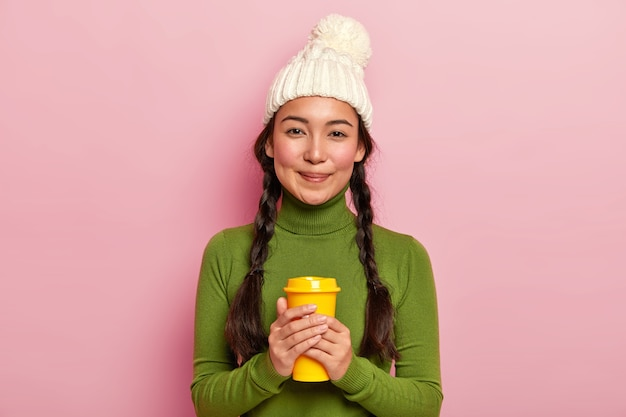 두 개의 땋은 머리를 가진 편안한 사랑스러운 검은 머리 여자, 테이크 아웃 커피를 들고, 겨울 동안 뜨거운 음료로 따뜻하게하고, 흰색 모자와 녹색 터틀넥을 착용합니다.