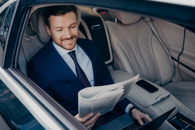 Relaxed male entrepreneur dressed in blue suit, reading latest newspaper and checking news regarding his successful company, while working on notebook, taking ride to work