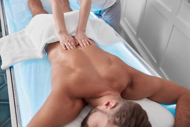 Relaxed male patient undergoes procedure of back massage lying in glowing couch