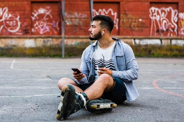 Relaxed male rollerskater with smartphone and disposal cup