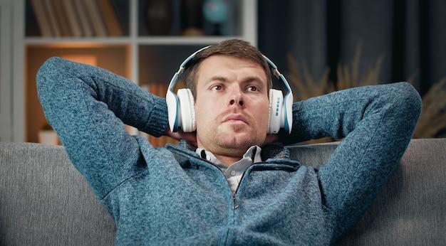 Расслабленный мужчина наслаждается музыкой в беспроводных наушниках, откидываясь назад на диване с руками за головой