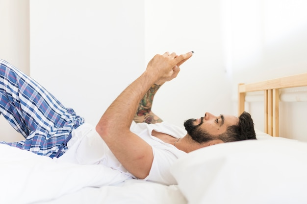 Relaxed man lying on bed using cellphone
