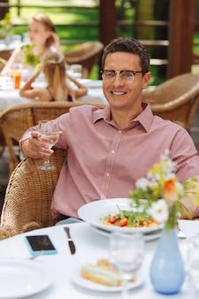 リラックスした男。夏のテラスでおいしいサラダを食べながら夕食を食べている間、非常にリラックスした感じの笑顔の男