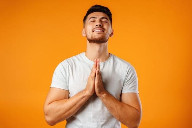 Расслабленный человек, стоящий в позе медитации на желтом фоне