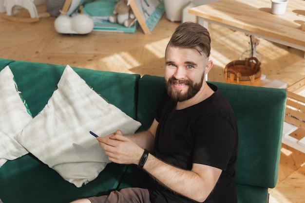집에서 거실에서 녹색 소파에 앉아 스마트 폰을 사용하는 편안한 남자