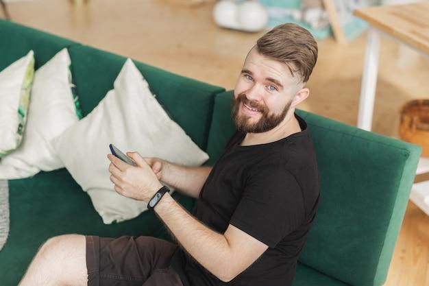 自宅の居間で緑のソファに座ってスマートフォンを使用してリラックスした男