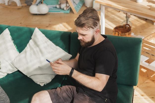 Расслабленный мужчина с помощью смартфона, сидя на зеленом диване в гостиной дома