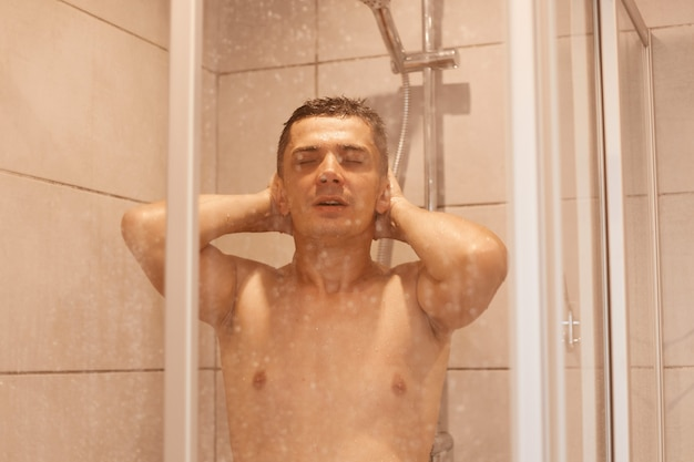 편안한 남자가 머리와 몸을 씻고 샤워실의 물 아래 서서 눈을 감고 있습니다. 위생 아침 절차, 화장실에서 알몸으로 포즈.