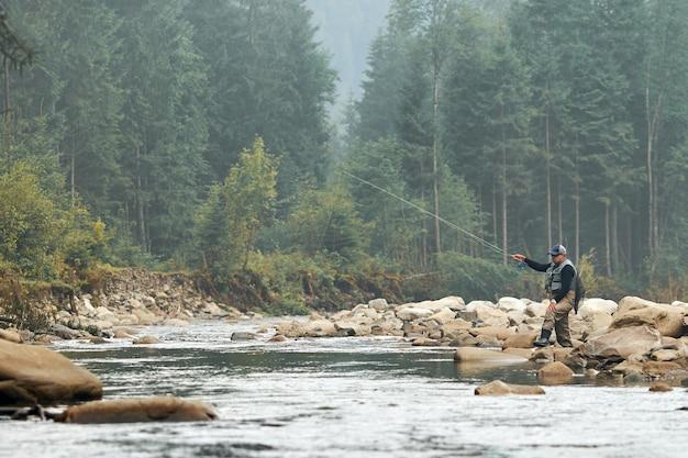 Расслабленный мужчина в специальной одежде во время рыбалки на бурной реке среди красивых гор. понятие о рыболовстве и досуге на природе.