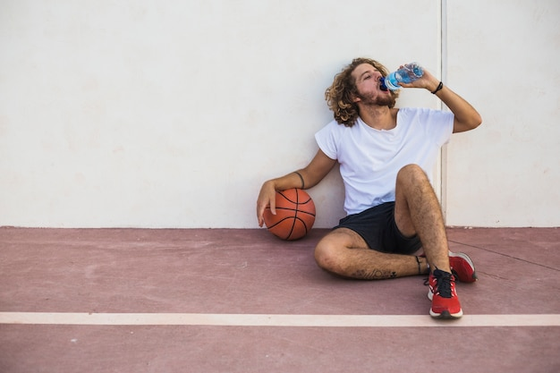 Relaxed man with basketball drinking water