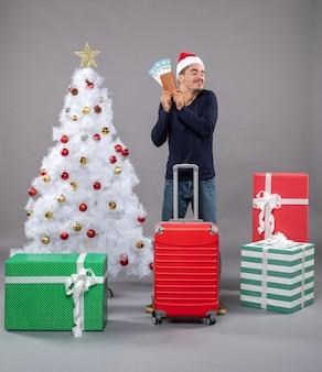 Uomo rilassato con la valigia rossa che mostra i suoi biglietti di viaggio su grigio