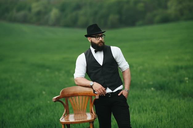 Расслабление человек с жилетом и шляпу рядом с деревянным стулом