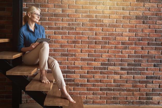 座っている間タブレットpcを使用して目をそらしている眼鏡をかけているリラックスした成熟した金髪の白人女性