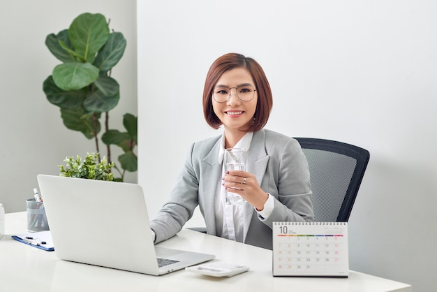Relaxed mature businesswoman holding glass of water and working on her laptop in the office