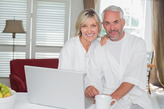 Relaxed mature couple with laptop at home