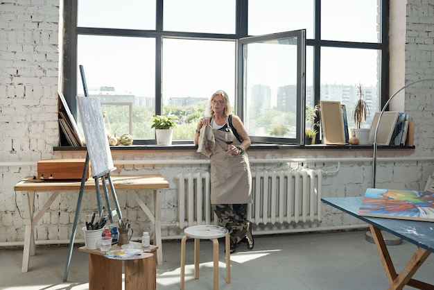 窓際に立って、アートスタジオでワインを飲むエプロンでリラックスした成熟した女性アーティスト