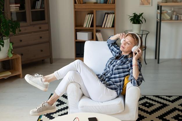 편안한 안락 의자에 앉아 가정 환경에서 음악을 즐기는 흰색 청바지, 운동화 및 체크 무늬 셔츠에 편안한 성숙한 여인