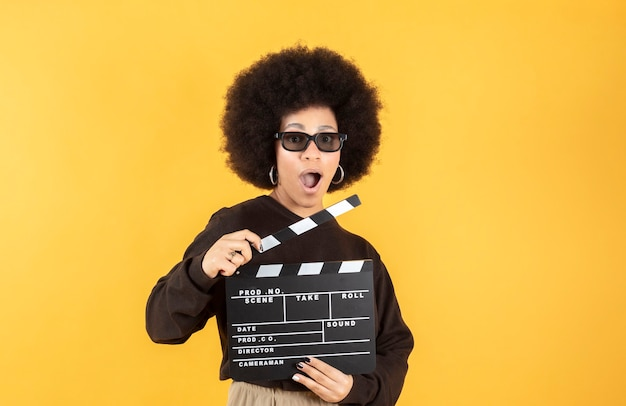 Relaxed mixed afro beautiful young woman in eyeglasses holds classic black film making clapperboard isolated on yellow background