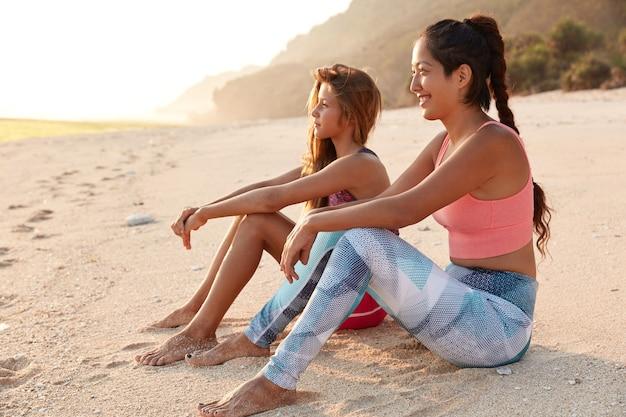 Giovani donne rilassate di razza mista in abiti sportivi, posa sulla sabbia, respirano l'aria marina