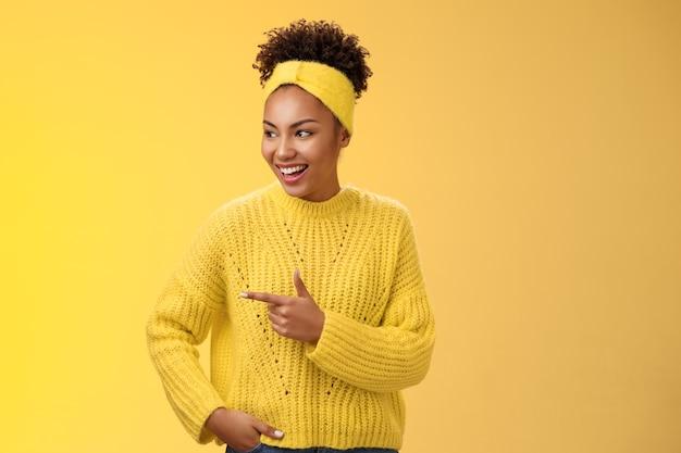 Lo spettacolo di ragazze afro-americane millenarie moderne e rilassate sembra interessante promo divertente che punta l'indice sinistro ridacchiando tenere la tasca della mano posa casual sicura di sé, in piedi sfondo giallo parlando.
