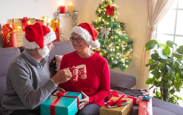 リラックスしたひとときと、幸せそうに見つめ合うサンタクロースの帽子をかぶった2人の高齢者のためのお茶。背景にはたくさんのプレゼントとクリスマスツリー