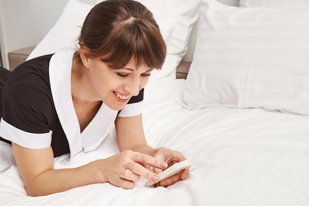 직장에서 편안한 순간. 침대에 기대어 브라우징 또는 스마트 폰을 통해 메시징, 미소하고 호텔 방을 청소하는 동안 좋은 분위기에 긍정적 인 하녀의 클로즈 업 초상화