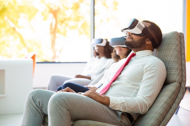 Relaxed multiethnic business colleagues in vr headsets