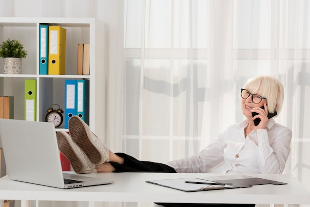 Relaxed old woman with eyeglasses sitting on her office