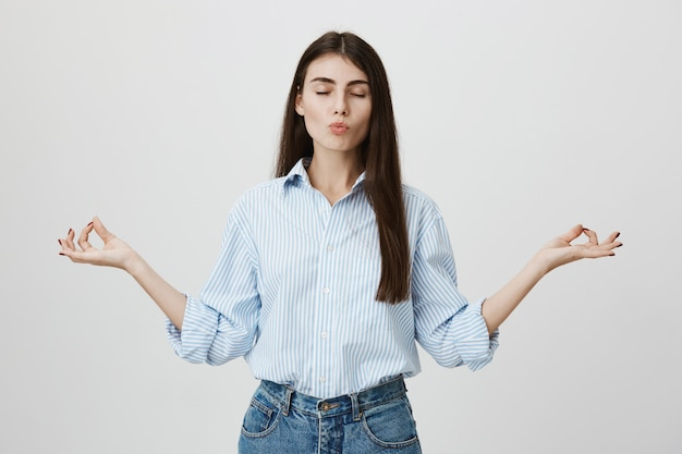 Relaxed, patient attractive businesswoman meditating with closed eyes