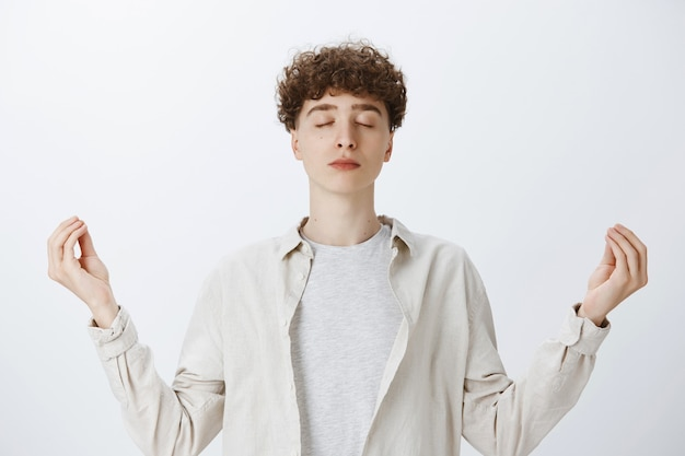 Relaxed patient teenage guy posing against the white wall