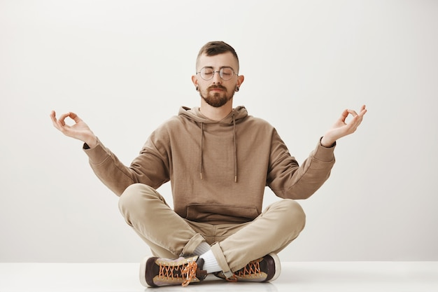 Relaxed peaceful hipster guy sit on floor and meditating, keep calm
