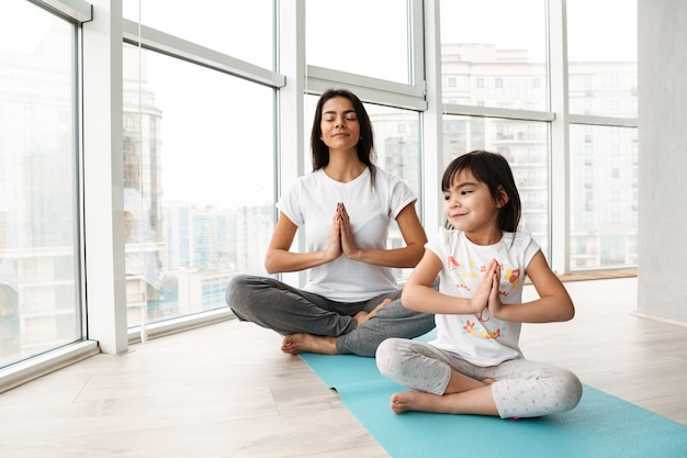 Relaxed people woman and kid practicing yoga indoor, sitting legs crossed on mat and keeping palms together