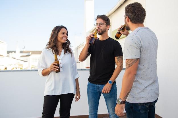 Расслабленные позитивные друзья наслаждаются вечером и пьют пиво
