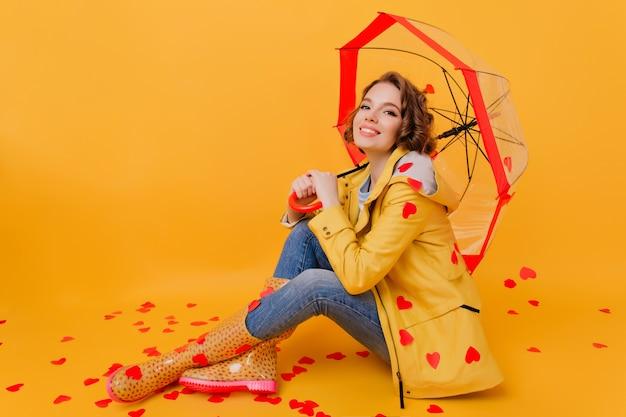 종이 마음을 잡고 노란색 코트에 편안한 예쁜 여자. 발렌타인 데이 사진 촬영 중 파라솔 아래에 앉아 멋진 짧은 머리 여자의 실내 사진.