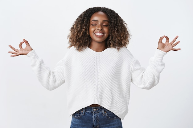 Rilassata sollevata donna afro-americana inspira aria sorridente felice meditando occhi chiusi mostrano sfere, gesto nirvana, posa del loto muro bianco