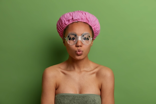Relaxed satisfied woman keeps lips folded, wears rubber eyewear, waterproof hat, wrapped in soft towel, takes shower, closes eyes, isolated on vivid green wall. hygiene, wellbeing, lifestyle