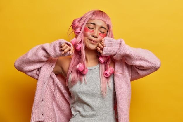 La donna rilassata e soddisfatta si allunga e si alza soddisfatta, tiene gli occhi chiusi, indossa un caldo maglione lavorato a maglia, chiude gli occhi, fa l'acconciatura riccia