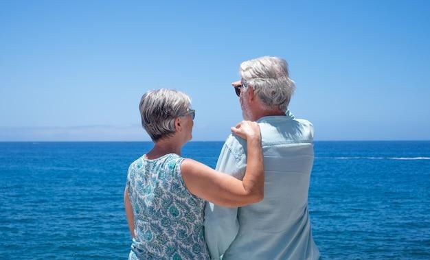 바다 앞에서 여름과 휴가를 즐기는 물 위로 수평선을 바라보는 편안한 노부부