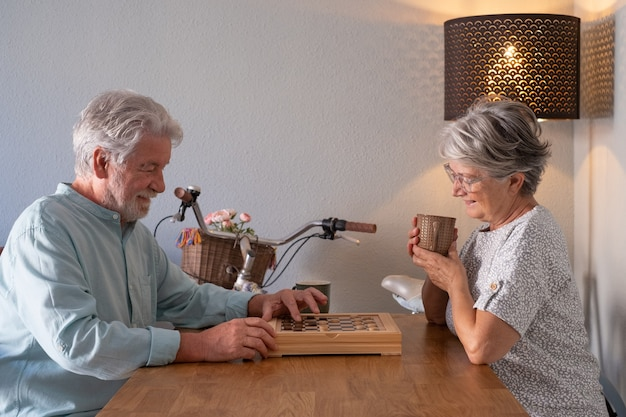 Relaxed senior couple spend time together at home playing a game of checkers on wooden table.