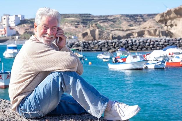 Расслабленный старший мужчина сидит в порту с помощью своего смартфона. привлекательные пожилые люди улыбаются, наслаждаясь природой и красотой природы. рыбацкие лодки и побережье на заднем плане